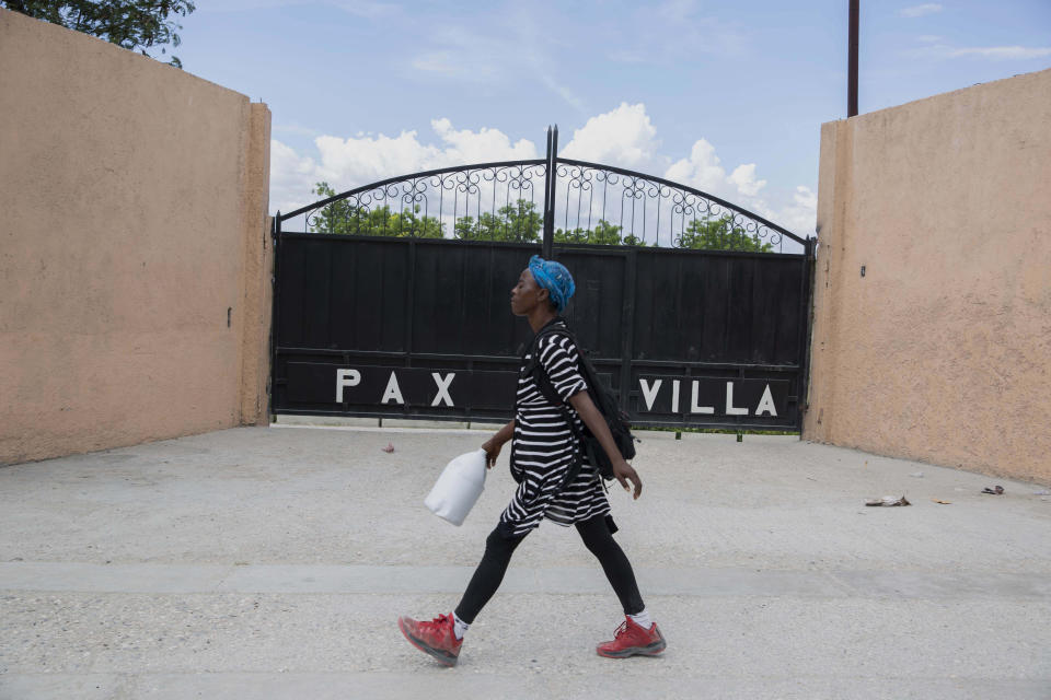 A woman walks past the entrance of the mortuary where the body of President Jovenel Moise was transferred to, in Port-au-Prince, Haiti, Saturday, July 10, 2021, three days after President Jovenel Moise was assassinated in his home . (AP Photo / Joseph Odelyn)