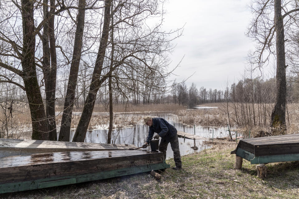"Yevgeny Markevich, an 85-year-old former teacher, repairs a boat near his house at the Chernobyl exclusion zone, Ukraine, Wednesday, April 14, 2021. Markevich said ""It's a great happiness to live at home, but it's sad that it's not as it used to be."" Today, he grows potatoes and cucumbers on his garden plot, which he takes for tests ""in order to partially protect myself."" The vast and empty Chernobyl Exclusion Zone around the site of the world's worst nuclear accident is a baleful monument to human mistakes. Yet 35 years after a power plant reactor exploded, Ukrainians also look to it for inspiration, solace and income. (AP Photo/Evgeniy Maloletka)"