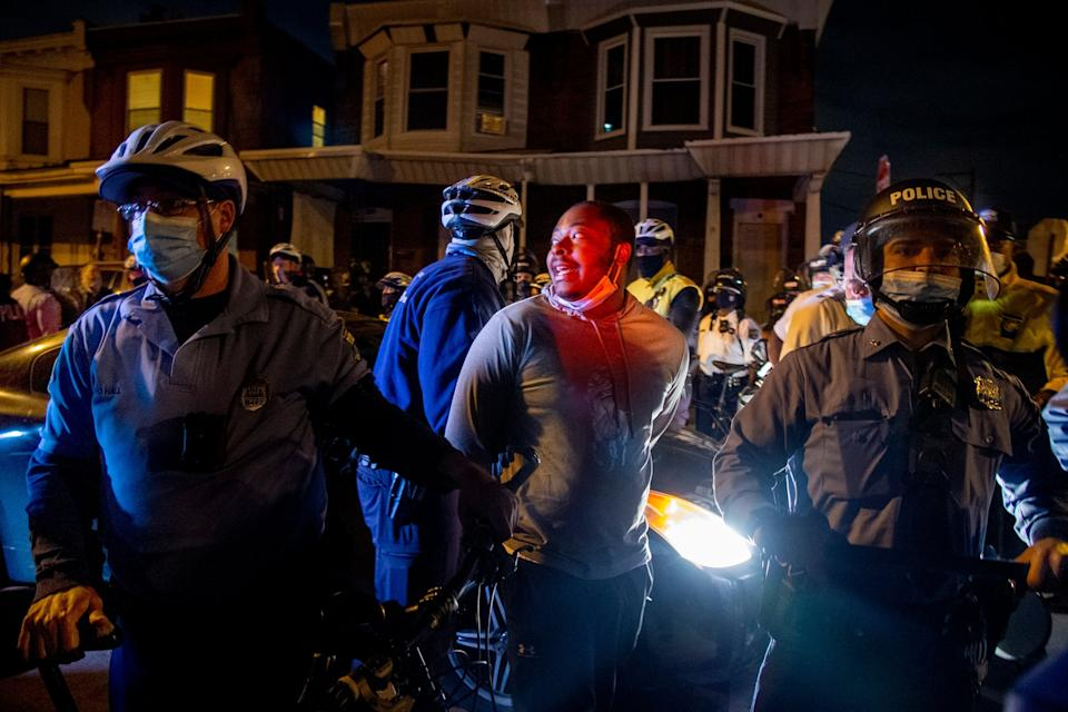 A person is handcuffed and detained by police in Philadelphia, after the citywide curfew had passed (AP)