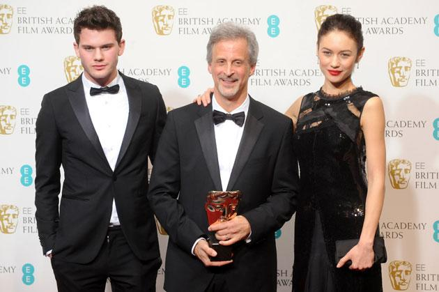William Goldenberg (C), winner of the Editing award for 'Argo', poses in the press room with presenters Jeremy Irvine (L) and Olga Kurylenko at the EE British Academy Film Awards at The Royal Opera House on February 10, 2013 in London, England. (Photo by Stuart Wilson/Getty Images)
