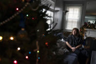 Eileen Carroll sits for a portrait in her home in Warwick, R.I, Wednesday, Dec. 16, 2020. When Carroll's daughter tested positive for the coronavirus, state health officials told her to notify anyone her daughter might have been around. Contact tracers, she was told, were simply too overwhelmed to do it. It's the same story across the U.S., as a catastrophic surge in infections has made it difficult or impossible to keep up with the calls considered critical to controlling outbreaks. (AP Photo/David Goldman)