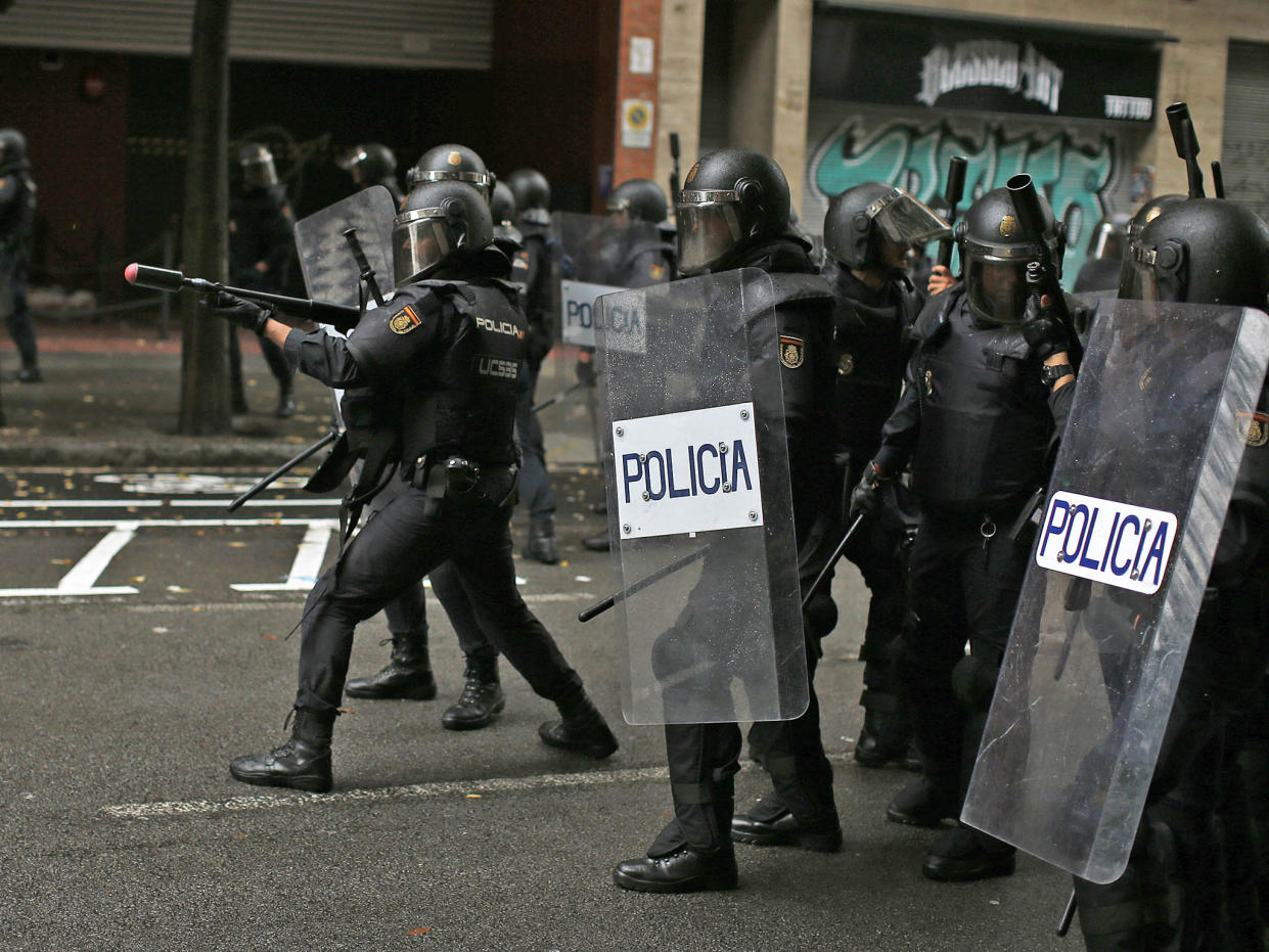A Spanish National Police officer aims a rubber-bullet rifle at pro-referendum supporters in Barcelona: AP