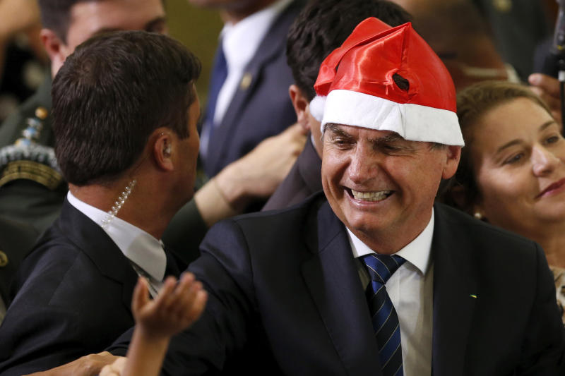 Brazil's President Jair Bolsonaro wears a Santa hat during the Christmas celebration with staff and students at the Planalto Presidential Palace, in Brasilia, Brazil, Thursday, Dec. 19, 2019. (AP Photo /Eraldo Peres)