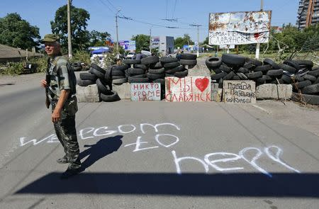 An armed pro-Russian separatist stands guard at check point in the Ukrainian eastern city of Slaviansk