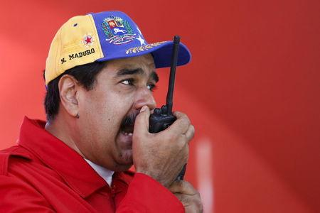 Venezuela's President Nicolas Maduro speaks on a walkie talkie during a visit to inspect the progress of a Metrocable station and a meeting with supporters in the Petare slum district of Caracas