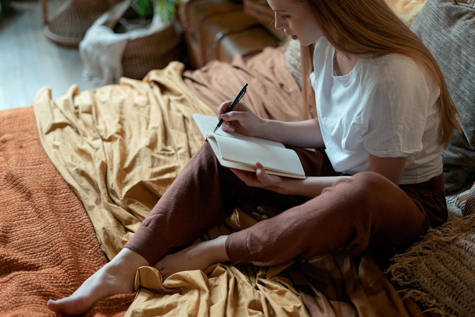 High angle view of thoughtful young adult girl writing notes in diary, sitting on bed, resting in home at cozy bedroom in boho style