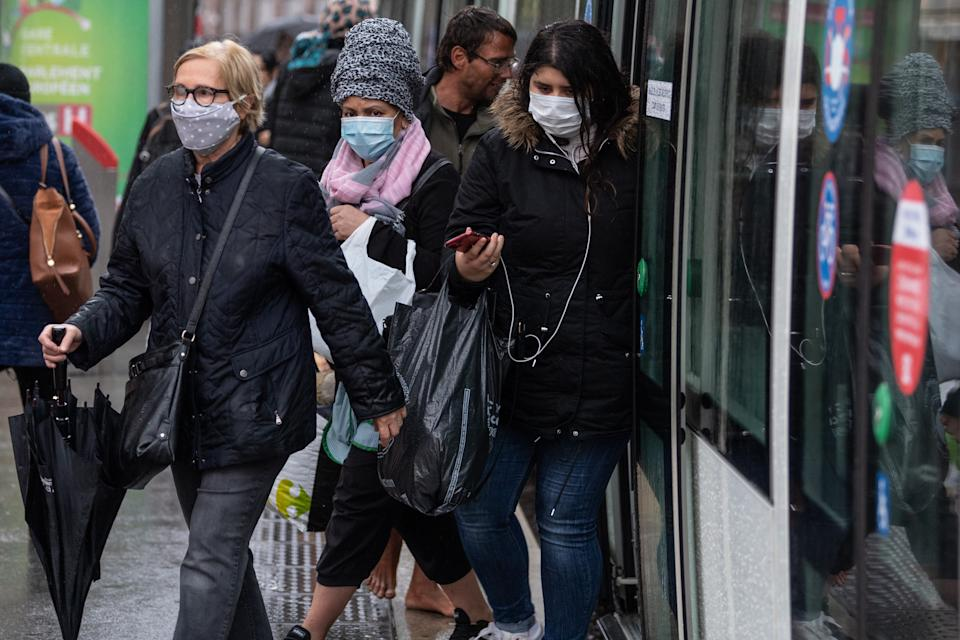 Passengers wearing a protective mask get out of a tram in central Strasbourg, eastern France, on May 11, 2020, on the first day of France's easing of lockdown measures in place for 55 days to curb the spread of the COVID-19 pandemic, caused by the new coronavirus. (Photo by PATRICK HERTZOG / AFP) (Photo by PATRICK HERTZOG/AFP via Getty Images)