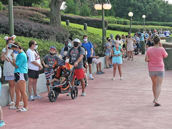 Guests wearing protective masks wait to pick up their tickets at the Magic Kingdom theme park at Walt Disney World on the first day of reopening, in Orlando, Florida, on July 11, 2020: Gregg Newton/AFP via Getty Image
