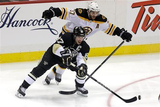Pittsburgh Penguins' Sidney Crosby (87) gets off a pass in front of Boston Bruins' Patrice Bergeron (37) in the first period of Game 1 of the NHL hockey Stanley Cup Eastern Conference finals in Pittsburgh, Saturday, June 1, 2013. (AP Photo/Gene J. Puskar)