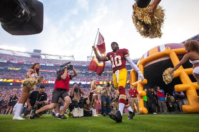 Washington Redskins quarterback, Roger Griffin III (10) comes onto the field from the tunnel to a cheering crowd before their NFL football game against the Philadelphia Eagles Monday, Sept. 9, 2013, in Landover, Md. (AP Photo/The Wilmington News-Journal, Suchat Pederson)