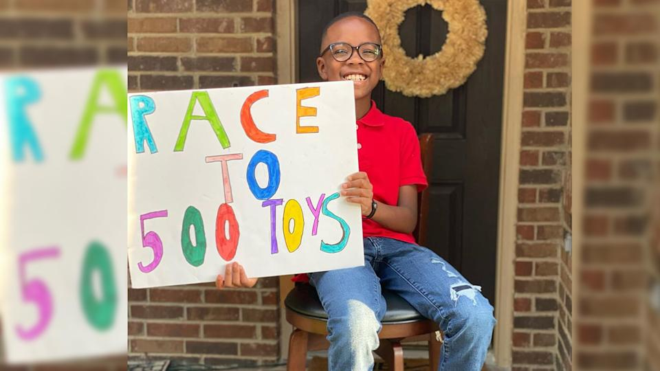 Orion Jean sits on a stool holding a sign that reads: Race to 500 toys.
