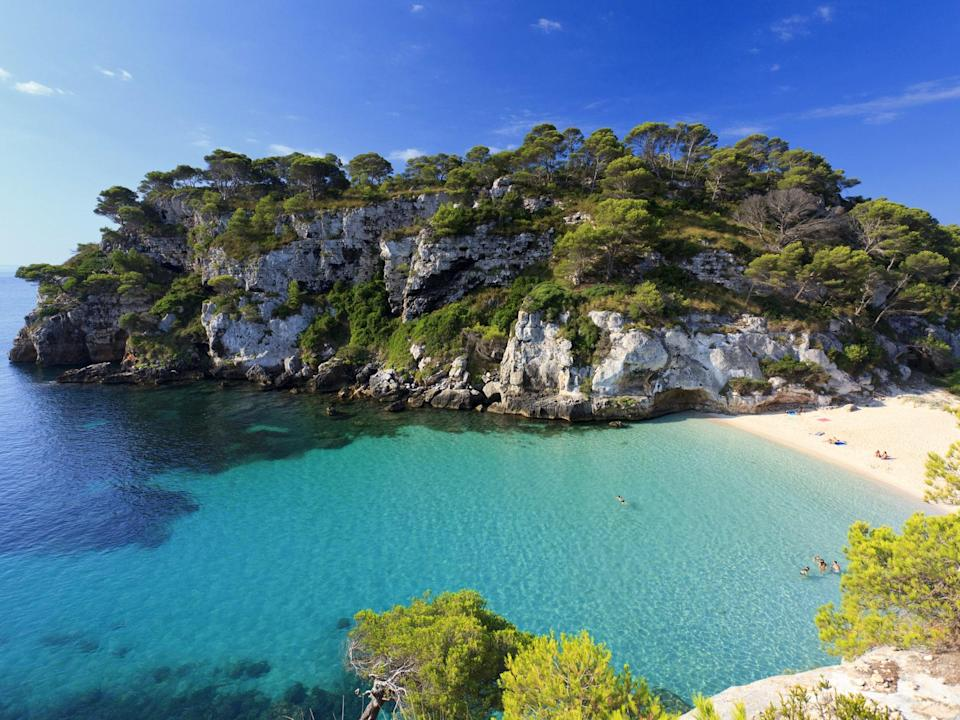 """Located on the sunny southwestern coast of Menorca, the tranquil Cala Macarella is the ideal escape from the congested beaches of nearby <a href=""""http://www.cntraveler.com/story/rafael-nadal-on-why-home-is-his-favorite-vacation-spot?mbid=synd_yahoo_rss"""" rel=""""nofollow noopener"""" target=""""_blank"""" data-ylk=""""slk:Mallorca"""" class=""""link rapid-noclick-resp"""">Mallorca</a> and <a href=""""http://www.cntraveler.com/story/designer-isabel-marant-on-decamping-to-ibizas-quiet-side?mbid=synd_yahoo_rss"""" rel=""""nofollow noopener"""" target=""""_blank"""" data-ylk=""""slk:Ibiza"""" class=""""link rapid-noclick-resp"""">Ibiza</a>. Getting there is a trek: you can either hike two miles along the cliffs from nearby Cala Galdana, or drive on a rough and winding road from Ciutadella and hike 20 minutes through a pine forest. But its ultra-fine sand and calm turquoise waters are worth the effort."""