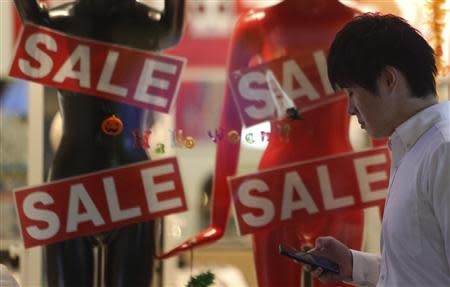 A man using a smart phone walks past a retail shop advertising a sale, in Tokyo October 1, 2013. REUTERS/Yuya Shino