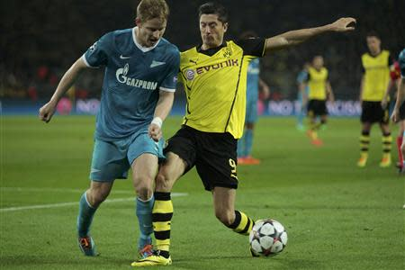 Zenit St Petersburg's Hubocan is tackled by Borussia Dortmund's Lewandowski during their Champions League round of 16 second leg soccer match in Dortmund