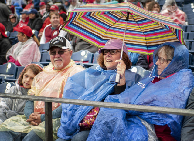 Spectators, from left right, Emma Gordy, and Robert Gordy, from Fredricksburg, Pa., Suzanne Taylor, from West Chester, Pa., and Sari Bollocking, from Coatesville, Pa., endure the rain during a baseball game between the Philadelphia Phillies and the Washington Nationals, Sunday, May 5, 2019, in Philadelphia. (AP Photo/Laurence Kesterson)