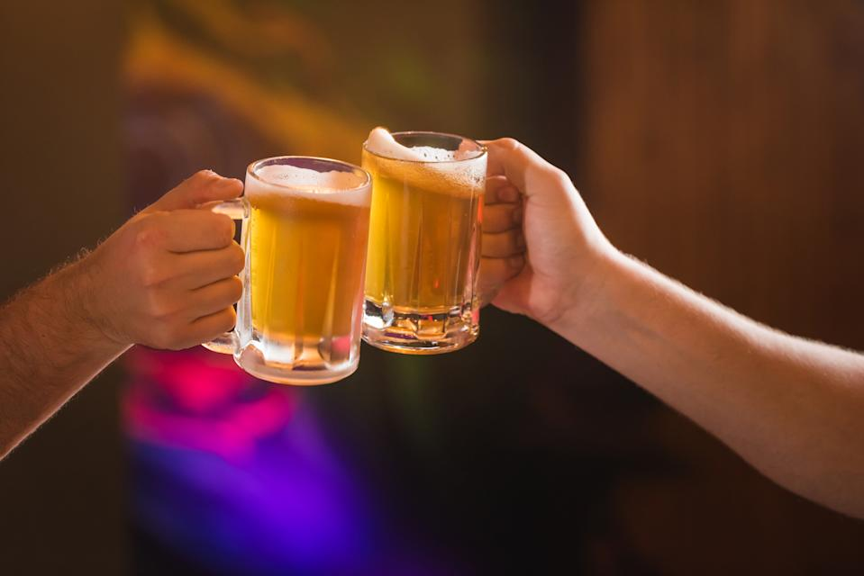 Two people toasting with mugs full beer
