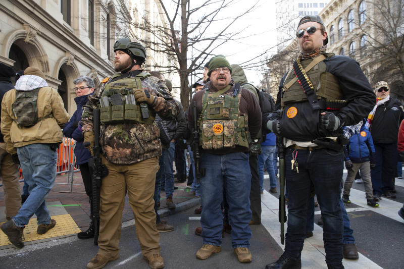 Gun-rights advocates, from Ohio, stand in downtown Richmond, Va., during a gun-rights rally at the Virginia State Capitol, Monday, Jan. 20, 2020. The rally was hosted by the Virginia Citizens Defense League but drew interest from groups across the country. (Mike Morones/The Free Lance-Star via AP)