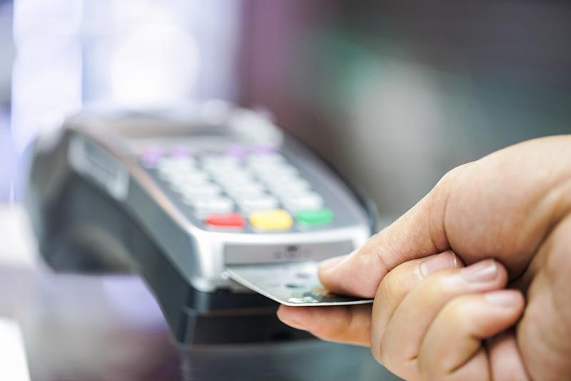 Credit card being inserted into a payment terminal.