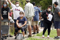 People wait in line at a free COVID-19 testing site provided by United Memorial Medical Center, at the Mexican Consulate, Sunday, June 28, 2020, in Houston. Confirmed cases of the coronavirus in Texas continue to surge. Texas Gov. Greg Abbott, on Friday, shut down bars again and scaled back restaurant dining as cases climbed to record levels after the state embarked on one of America's fastest reopenings. (AP Photo/David J. Phillip)