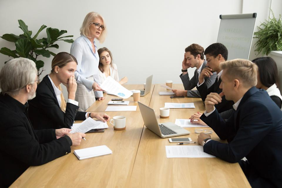 Dissatisfied boss scolding employees for bad work at group meeting,