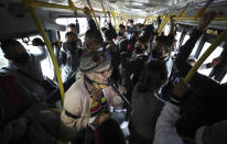 """Marlene Alfonso, a 69-year-old Venezuelan grandmother who goes by """"Toothless Cindy,"""" sings about Venezuelan migrants' lives in hopes of tips from commuters on the Transmilenio, the crowded and crime-ridden public bus system in Bogota, Colombia, Tuesday, Nov. 3, 2020. Some take selfies with the toothless grandmother, and others have posted videos of her singing on buses that have gone viral on Twitter. (AP Photo/Fernando Vergara)"""