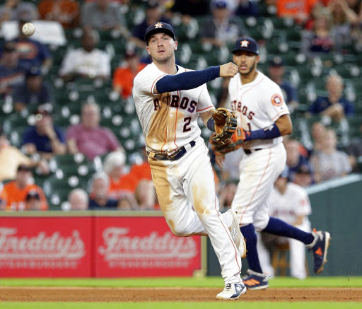 Houston Astros third baseman Alex Bregman (2) fields the hit by San Francisco Giants Evan Longoria as shortstop Carlos Correa (1) backs the play during the ninth inning of a baseball game Wednesday, May 23, 2018, in Houston. (AP Photo/Michael Wyke)