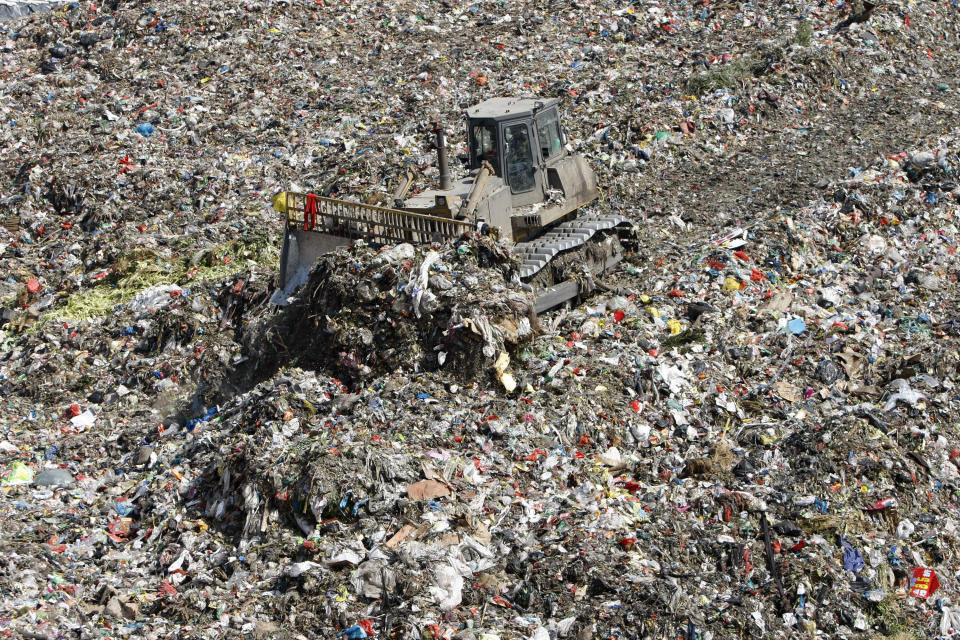 A bulldozer evens out garbage at a waste landfill site in Hangzhou, Zhejiang province March 11, 2010.  REUTERS/Steven Shi (CHINA - Tags: ENVIRONMENT)