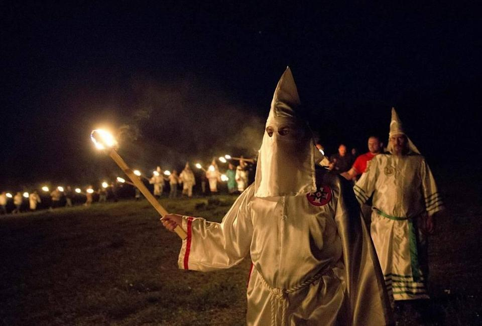 """Members of the Ku Klux Klan participate in cross burnings after a """"white pride"""" rally in rural Paulding County near Cedar Town, Ga. Born in the ashes of the smoldering South after the Civil War, the KKK died and was reborn before losing the fight against civil rights in the 1960s."""
