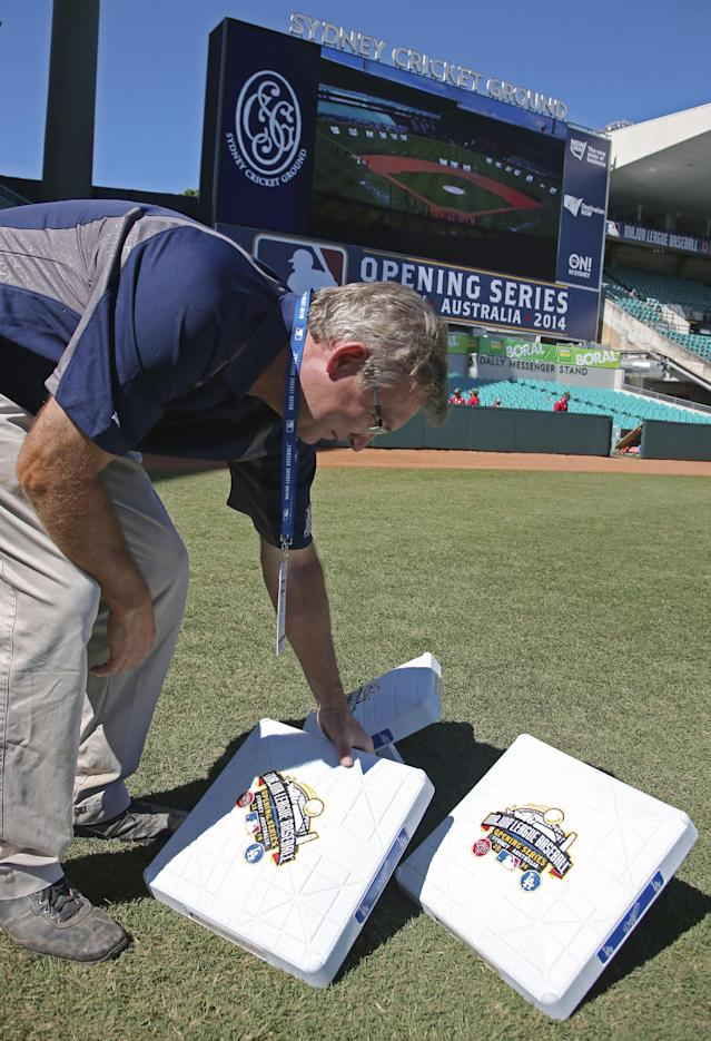 Murray Cook, the MLB field and stadium consultant, places on the field bases with commemorative logos on them as preparations are made for the Major League Baseball opening game between the Los Angeles Dodgers and the Arizona Diamondbacks at the Sydney Cricket ground in Sydney, Saturday, March 22, 2014. (AP Photo/Rick Rycroft)