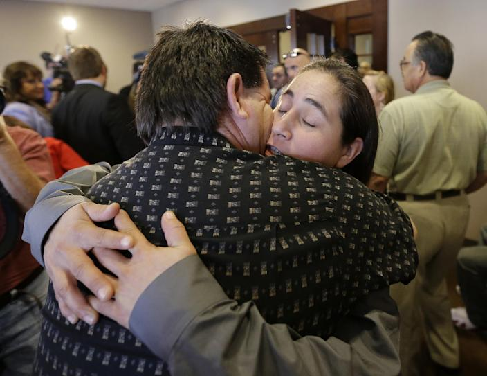 Anna Vasquez, right, is hugged by family as she leaves a courtroom at the Bexar County Courthouse, Monday, Nov. 18, 2013, in San Antonio, after it was announced that three of four San Antonio women imprisoned for sexually assaulting two girls in 1994 were expected to walk free after a judge agreed that their convictions were tainted by faulty witness testimony. Vasquez, the fourth woman, has already been paroled, but under strict conditions. (AP Photo/Eric Gay)