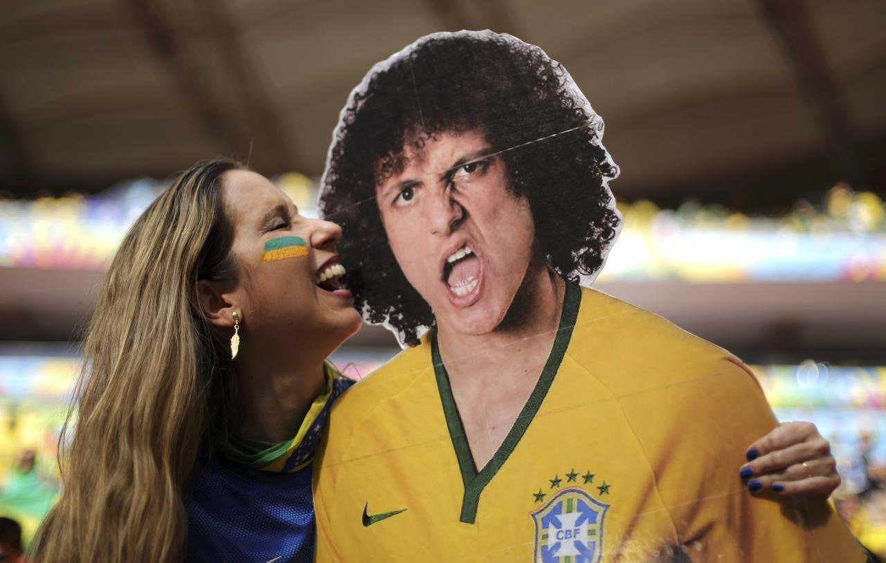 A fan poses with a picture of Brazil's David Luiz before the 2014 World Cup third-place playoff between Brazil and the Netherlands at the Brasilia national stadium in Brasilia July 12, 2014. REUTERS/Ueslei Marcelino (BRAZIL - Tags: SOCCER SPORT WORLD CUP)