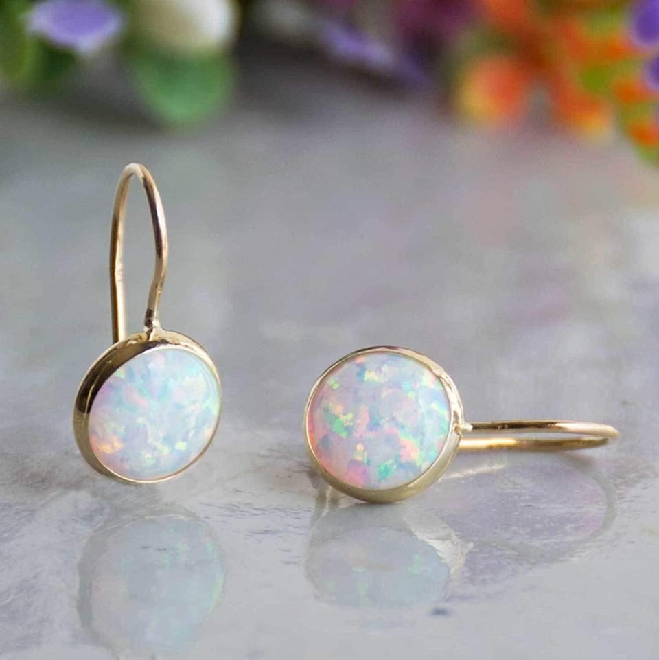 <p>These dainty <span>14k Solid Yellow Gold White Opal 8mm Gemstone Dangle Earrings</span> ($104) will elevate any look. This is a great gift to give, especially if they was born in October.</p>