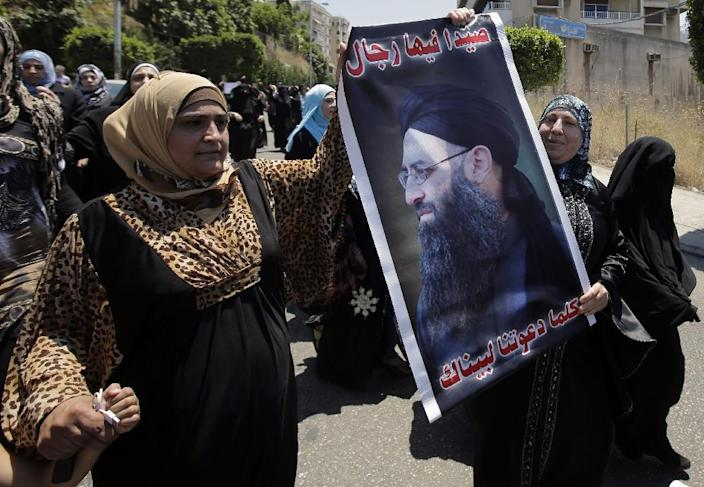 Supporters of Lebanese radical cleric Ahmad al-Assir hold a poster of him in the southern city of Sidon on July 5, 2013 (AFP Photo/Joseph Eid)