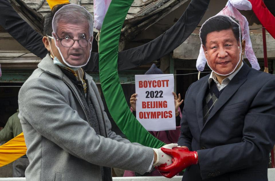 """<span class=""""caption"""">Activists wearing masks of IOC President Thomas Bach and Chinese President Xi Jinping pose in front of the Olympic Rings during a street protest in India against the holding of the 2022 Beijing Winter Olympics.</span> <span class=""""attribution""""><span class=""""source"""">(AP Photo/Ashwini Bhatia)</span></span>"""