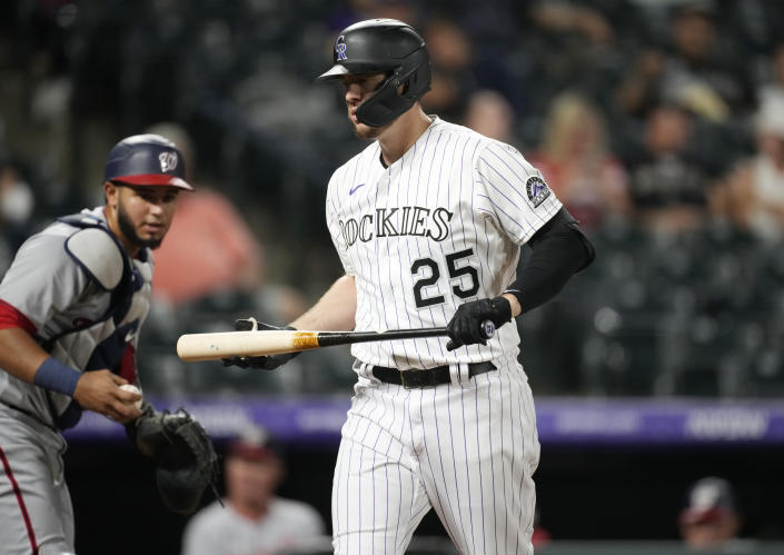 Colorado Rockies' C.J. Cron, right, reacts after striking out as Washington Nationals catcher Keibert Ruiz looks on in the fourth inning of a baseball game Monday, Sept. 27, 2021, in Denver. (AP Photo/David Zalubowski)