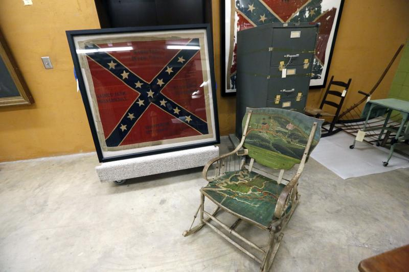 In this Oct. 11, 2013 photograph, a hand painted Civil War era double rocker, a Confederate regiment battle flag and a one-time sealed Sovereignty Commission file cabinet will eventually be displayed in either a Mississippi history museum or a civil rights museum in Jackson, Miss. Officials say they did not set out to have separate-but-equal museums for the documentation of the state's history, but it could end up that way. Groundbreaking is set for Oct. 24 for the Mississippi History Museum and the Mississippi Civil Rights Museum, side-by-side buildings, that when opened in 2017, may together tell the state's complex history. The two museums will have more than 200,000 square feet combined and are to be built not far from the Capitol in Jackson. The state has committed $40 million to the museums, and Holmes said officials are trying to raise $14 million in private donations. (AP Photo/Rogelio V. Solis)