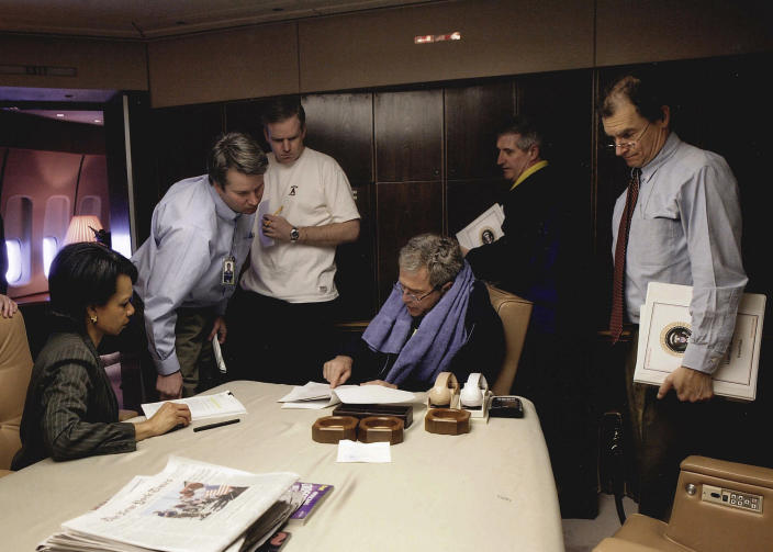 In this image provided by the Department of Justice, Brett Kavanaugh, second from left, talks with President George W. Bush, Secretary of State Condoleezza Rice, left, and Andy Card, second from right, aboard Air force One. Kavanaugh has been a conservative team player, and the Supreme Court nominee has stepped up to make a play at key moments in politics, government and the law dating to the Bill Clinton era. (Department of Justice via AP)