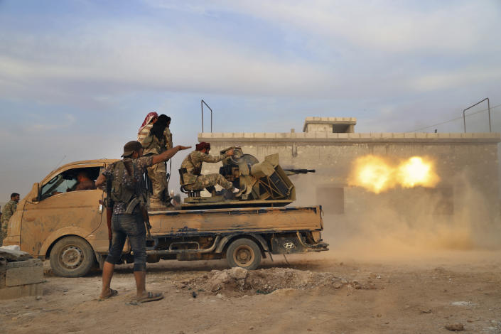 In this Monday, Oct. 14, 2019 photo, Turkey-backed Syrian opposition fighters fire a heavy machine-gun towards Kurdish fighters, in Syria's northern region of Manbij. Syrian state media said Tuesday that government forces have entered the center of the once Kurdish-held northern town of Manbij and raised the national flag. (AP Photo)