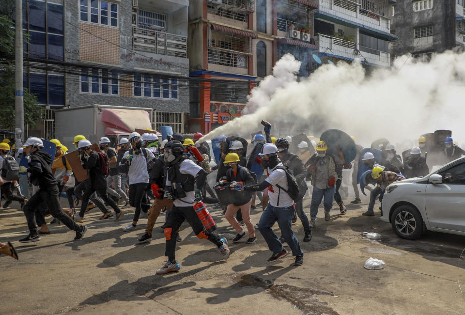 Anti-coup protesters run as one of them discharges a fire extinguisher to counter the impact of tear gas fired by riot policemen in Yangon, Myanmar, Wednesday, March 3, 2021. Demonstrators in Myanmar took to the streets again on Wednesday to protest last month's seizure of power by the military. (AP Photo)