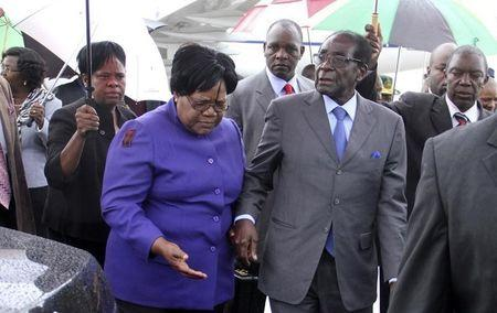 Zimbabwean President Robert Mugabe is greeted by Vice President Joice Mujuru as he returns home to Harare