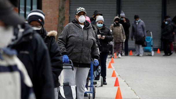PHOTO: People wearing protective masks wait in line for donated food distribution at the Queensbridge Houses, a public housing complex, during the outbreak of the coronavirus disease (COVID-19) in the Queens borough of New York, April 21, 2020. (Andrew Kelly/Reuters)