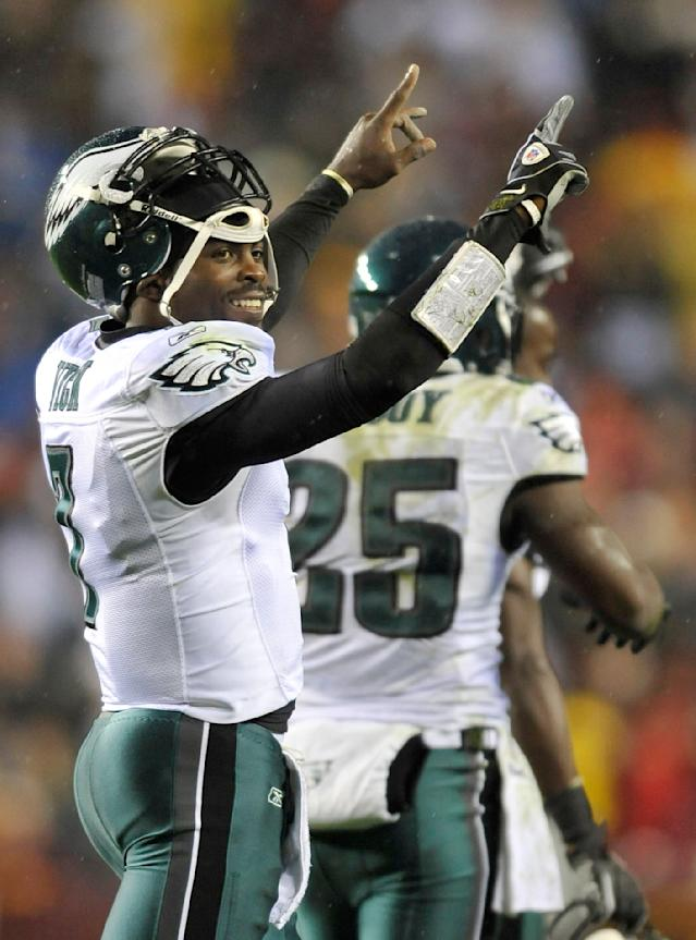 FILE - In a Nov. 15, 2010 file photo, Philadelphia Eagles quarterback Michael Vick celebrates after throwing a touchdown pass to wide receiver Jeremy Macli during the first half of an NFL football game against the Washington Redskins, in Landover, Md. The New York Jets signed quarterback Michael Vick and released Mark Sanchez on Friday, March 21, 2014. Vick was a free agent after spending the last five seasons with the Phialdelphia Eagles. (AP Photo/Gail Burton, File)