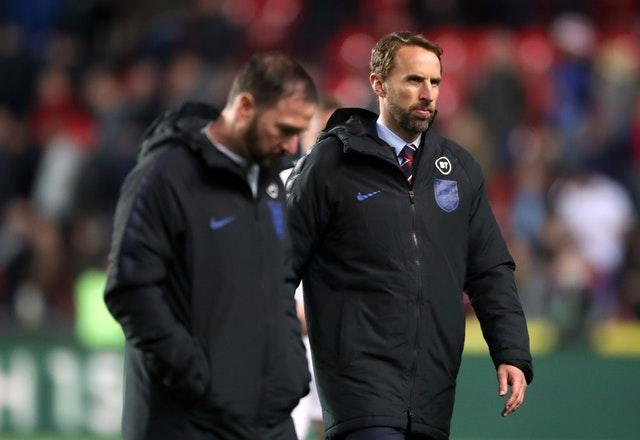 Southgate and his assistant Steve Holland walk off the pitch dejected after the match