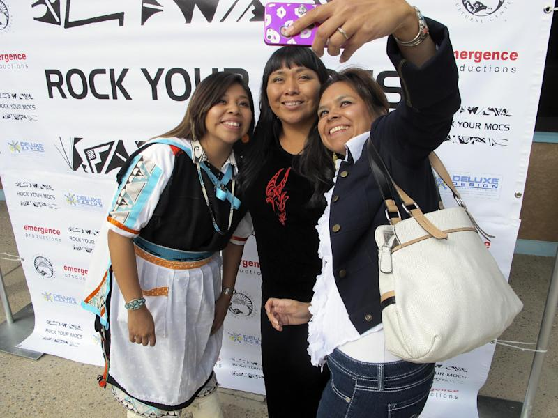 """""""Rock Your Mocs"""" creator Jessica """"Jaylyn"""" Atsye of Laguna Pueblo, left, Melissa Sanchez, center, and Antonia Gonzales take a photo during the """"Rock Your Mocs"""" celebration at the Indian Pueblo Cultural Center in Albuquerque, N.M., on Friday, Nov. 15, 2013. The social media campaign has gone global with Native American and indigenous people from as far away as New Zealand participating. (AP Photo/Susan Montoya Bryan)"""