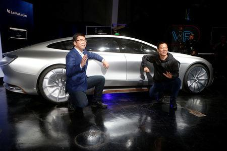 LeEco CEO and founder YT Jia, R, and co-founder and Global Vice Chairman Lei Ding pose in front of a LeSEE car during a press event in San Francisco