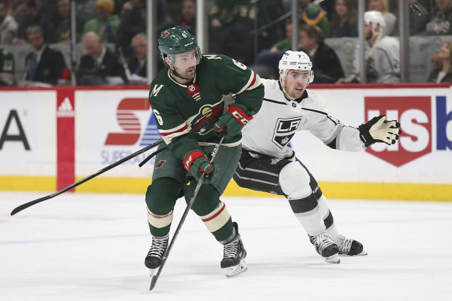 Minnesota Wild's Ryan Murphy (6) keeps his eyes on an airborne puck against Los Angeles Kings' Tanner Pearson (70) in the second period of an NHL hockey game Monday, March 19, 2018, in St. Paul, Minn. (AP Photo/Stacy Bengs)