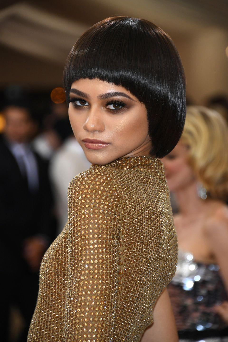 "<p>Zendaya rocked a bowl cut with bronze makeup at the ""Manus x Machina: Fashion In An Age of Technology"" Met Gala.</p>"