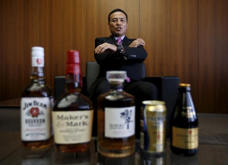 Suntory Holdings Ltd's President and CEO Takeshi Niinami speaks behind the company's alcoholic beverages during an interview with Reuters at the company headquarters in Tokyo