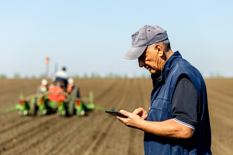 A farmer in a field with a tractor behind him