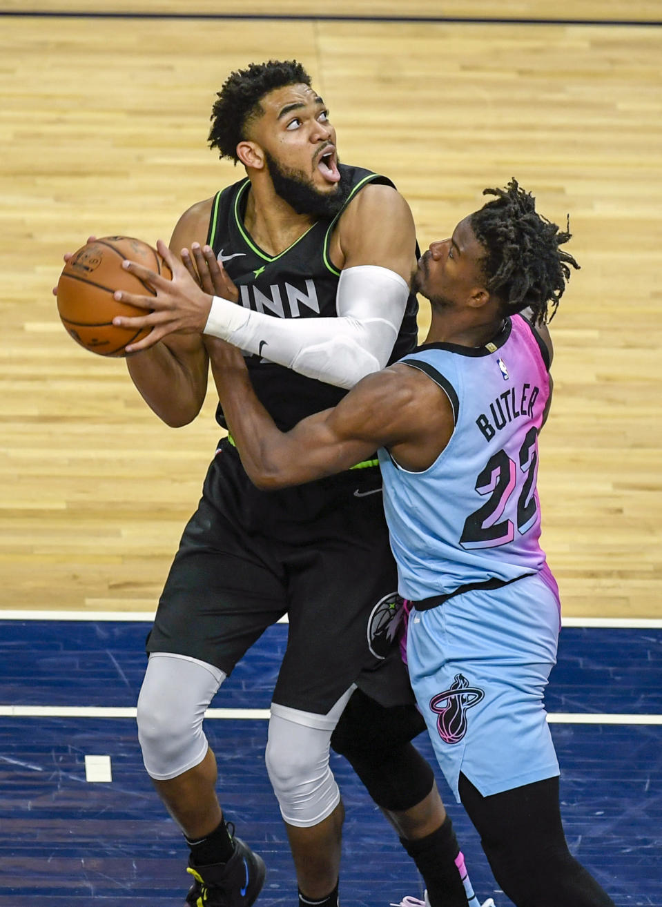 Minnesota Timberwolves center Karl-Anthony Towns, left, is fouled by Miami Heat forward Jimmy Butlerduring the second half of an NBA basketball game Friday, April 16, 2021, in Minneapolis. The Timberwolves won 119-111. (AP Photo/Craig Lassig)